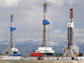 Photo of three natural gas drilling rigs.