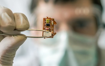 A scientist holds an electronic circuit with a set of tweezers.