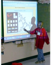 A middle school student pointing to a screen projection describes a mathematical image.