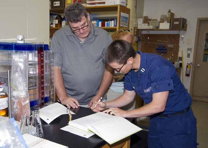 Image of two people preparing the Gulf sample to take to Woods Hole Oceanographic Institution.