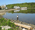 Photo of Lyndie Hice checking water temperature and salinity along the coast of Maine.