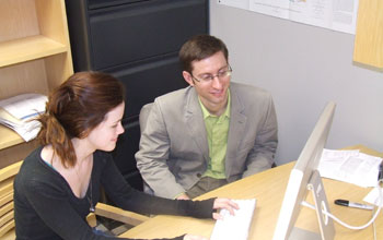 Photo of scientists Jacob Sewall and Elizabeth Heness analyzing climate change simulations.