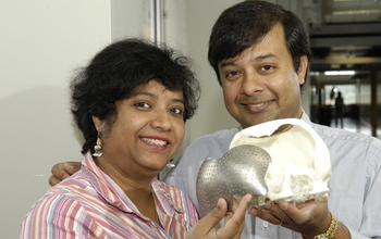 Engineers holding a skull with artificial implant