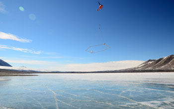 Photo of a helicopter carrying SkyTEM mapping technology over Lake Fryxell in Antarctica.