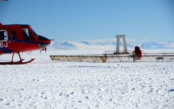 Photo of a helicopter preparing to launch SkyTEM mapping technology on the Antarctic sea ice.