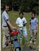 Photo of researchers sampling arthropods from sleepy grass with the Burkhard Vortis suction sampler.