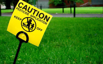 A yellow sign saying Caution pesticide application standing out of a green lawn
