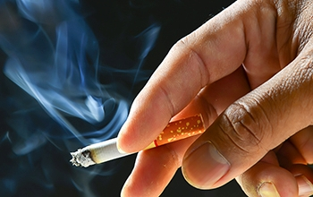 a lit cigarette between a person's fingers