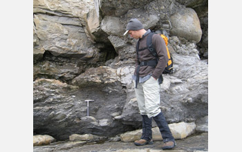 Photo of Geologist Noah Plavansky examining rocks deposited after a Snowball Earth glacial event.