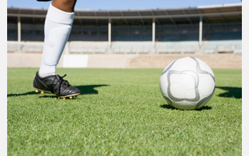 Photo showing the leg of a soccer player and a soccer ball.