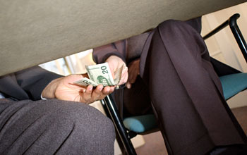 Photo of a man handing two twenty dollar bills to another man beneath a table.