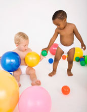 two young children playing with balls.