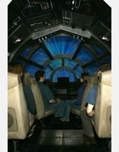 Photo of visitors seated at a full-size replica of the Millennium Falcon cockpit.