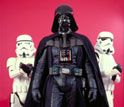 Photo of Darth Vader with stormtroopers holding blasters.