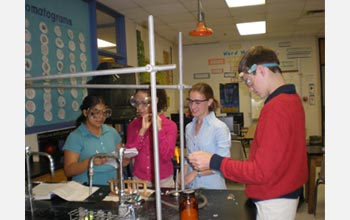 Photo of teacher and students in chemistry lab.