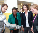 Photo of Cora Marrett, Dahlia Sokolov and Joan Ferrini-Mundy interact with humanoid robot.