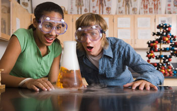 Image of two school children with their mouths open looking at a liquid- and gas-filled flask .
