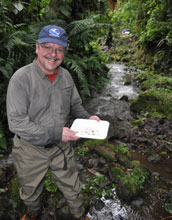 Photo of scientist LeRoy Poff sampling aquatic insects along a vine-choked stream in Ecuador.