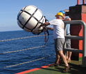 Photo of researcher Jamie Austin deploying a sound source and wave recorder.