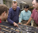Photo of Chad Broyles, Jorg Geldmacher, Takashi Sano and Will Sager looking at a Shatsky Rise core.