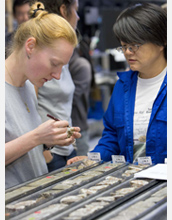 Photo of scientists Adelie Delacour and Chieh Peng working at the onboard sampling table.