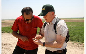 Photo of project co-directors Annas and Gil Stein examining a sherd of pottery at Tell Zeidan.