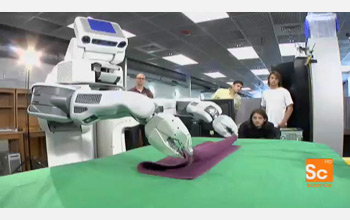 Image of the robot PR2 folding a towel.