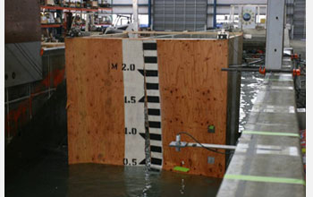 Photo showing a wooden shear wall upon failure caused by a 0.7m high tsunami wave breaking on wall.