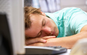 Image of a man sleeping on a table in front of the keyboard and monitor of his workstation.