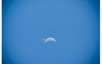Photo of  AUAV involved in the Maldives project flying by the moon in a blue sky.