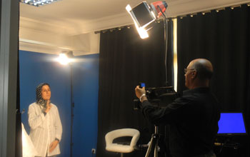 A videographer and a Moroccan Sign Language interpreter record signs in a studio