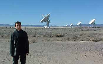 Young man stands in front of a row of white telescopes.