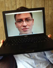 Image of Luis von Ahn holding a laptop blocking his face with an image of his face in the monitor.