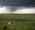 Photo of researchers studying a tornado from a safe distance away.