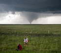 Researchers in the field studying a tornado in the distance.