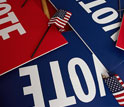 Photo of a pile of red and blue VOTE signs.