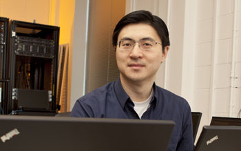 Mung Chiang in his office surrounded by computers.