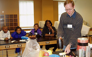Researcher is about to smash a banana while several children and an adult watch the demonstration.