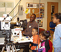A researcher shows three kids how materials look through the lens of a microscope