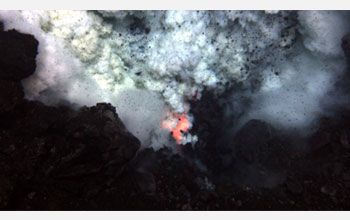 Photo of an explosion of ash and rock at the West Mata Volcano with molten lava glowing below.