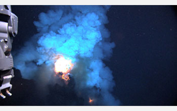 Photo of  a bright flash of hot magma blown up into the water before settling back to the seafloor.