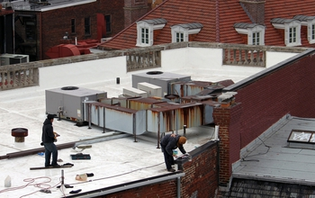 Painters working on a Washington, D.C., roof to make it a light-reflecting white.