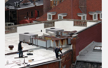 Photo of a construction crew painting a white roof in downtown Washington, D.C.