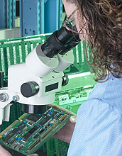 woman looking at computer chips through a microscope