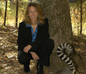 Photo of Duke University Lemur Center Director Anne D. Yoder kneeling with a ring-tailed lemur.