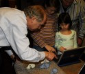 Photo of researcher showing children tiny model skulls and computer models