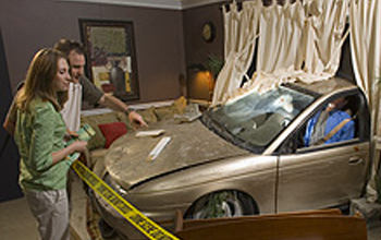 Photo of two guests observing a crime scene exhibit featuring a car that collided with a house