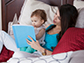 a mother and child in bed reading a book