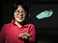 Wu-Jung Lee holds a skull of an Egyptian fruit bat; on the screen is the 3-D mesh of a fruit bat's head