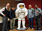 researchers pose with a model of an astronaut